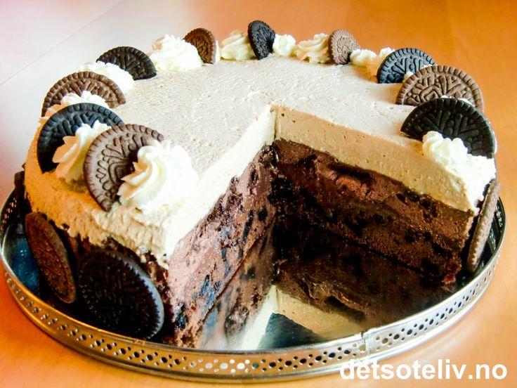 Kaken du ser her er en egenkomposisjon, og min STORE STOLTHET! Dette er virkelig en drøm av en sjokolademoussekake for deg som også liker litt kaffesmak i sjokoladekaker. Tanken var å lage en kake med eksklusivt utseende og som består av sjokolade i flere former og brunfargenyanser. Som bunn har jeg brukt en deilig, mørk og litt fudgy sjokoladebrownie. Alt over browniebunnen er fløyelsmyke ting: første et lag sjokoladepudding og så et lag lys sjokolademousse og til slutt et lag helt lysebrun…
