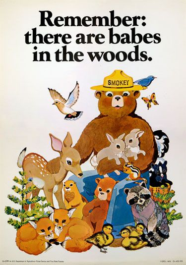 """Smokey Bear poster showing Smokey holding two tan rabbits. Surrounding him there is a blue bird, a tan and blue bird, a orange and black butterfly, a skunk, a raccoon, three yellow ducks, two foxes, a cub, a chipmunk, a deer, what appears to be a beaver, and two small trees. Poster reads """"Remember there are babes in the woods."""""""