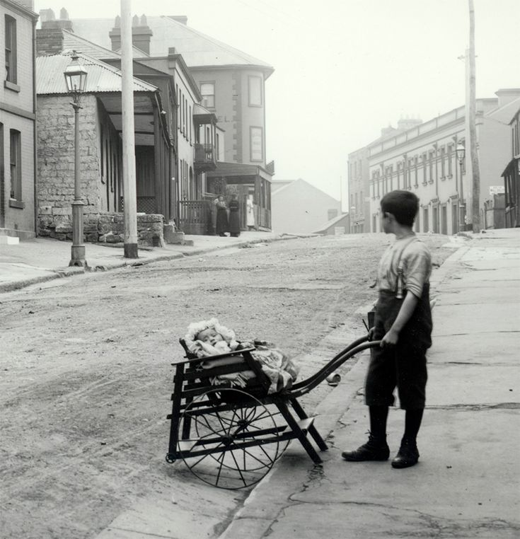 Boy pushing pram on Gloucester Street, The Rocks, Sydney, Australia c1900