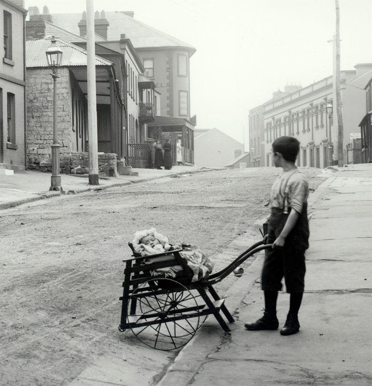 Boy pushing pram on Gloucester Street, The Rocks, Sydney, Australia c1900