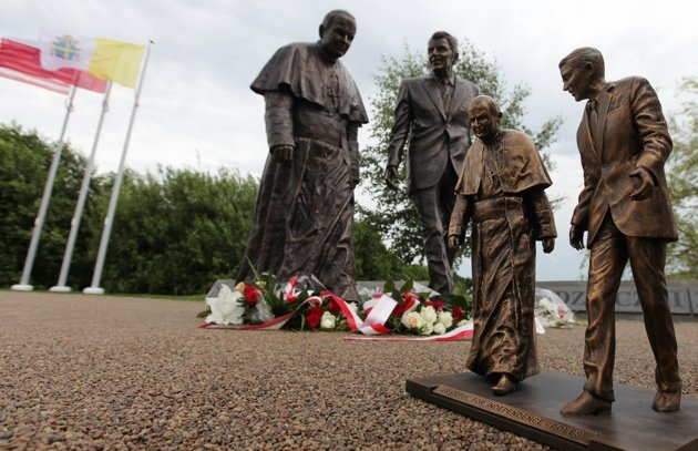 A miniature stands in front of the new statue of former President Ronald Reagan and Pope John Paul II that was unveiled in Gdansk, Poland, on Saturday, July 14, 2012. The statue honors the two men who