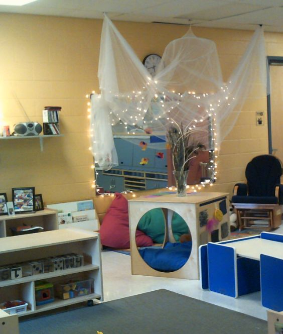 Le Centre de L'Enfant Ange-Gabriel- A quiet area in a toddler room is created by adding large cushions, a hiding cube and a mosquito net with light strings attached.