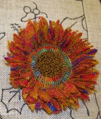 sunflower pin! The center was rug hooking but can change to felt or fabric. Using fibers on the edges, simply sew in & out making loops and then cut to make short to long. no need to know.