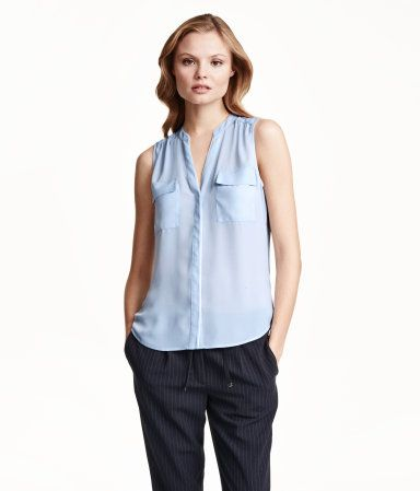 Sleeveless V-neck blouse in an airy, woven fabric. Concealed buttons at front, two chest pockets, and gently rounded hem.