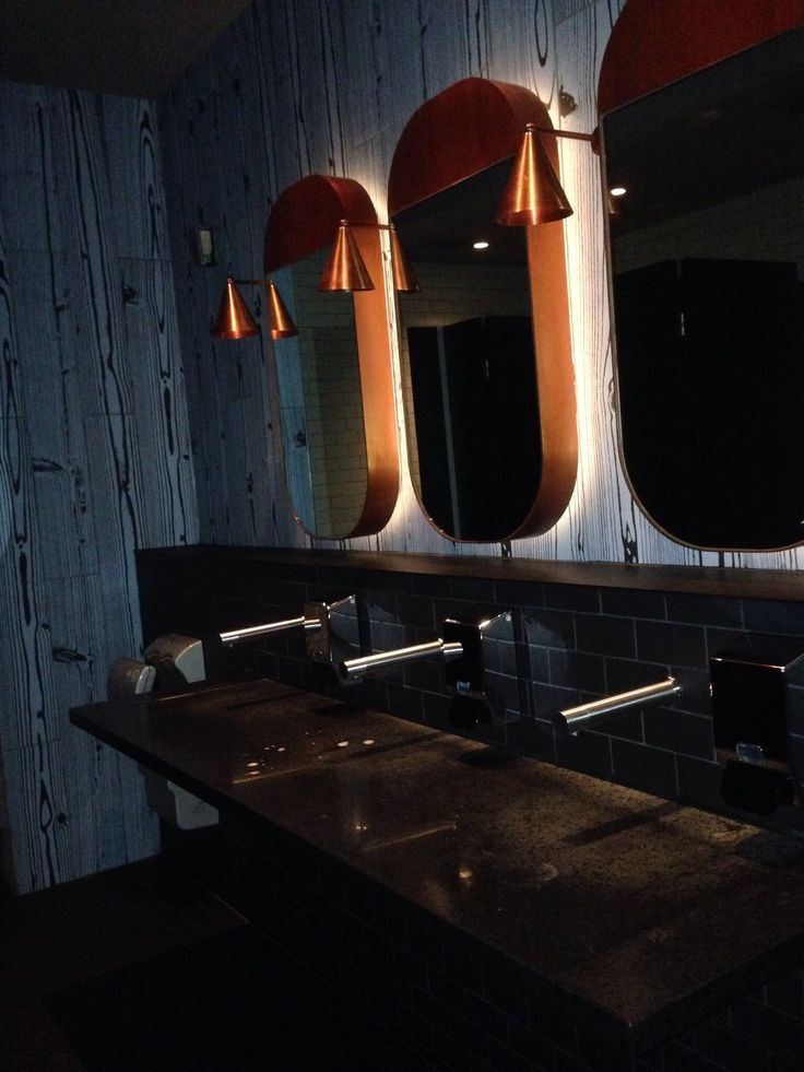 The dark restroom gives almost a nightclub feel. The dark granite basins and silver chrome tap wear are perfect together. The copper light fittings finish it off with there brassy red reflection off the mirror frames.