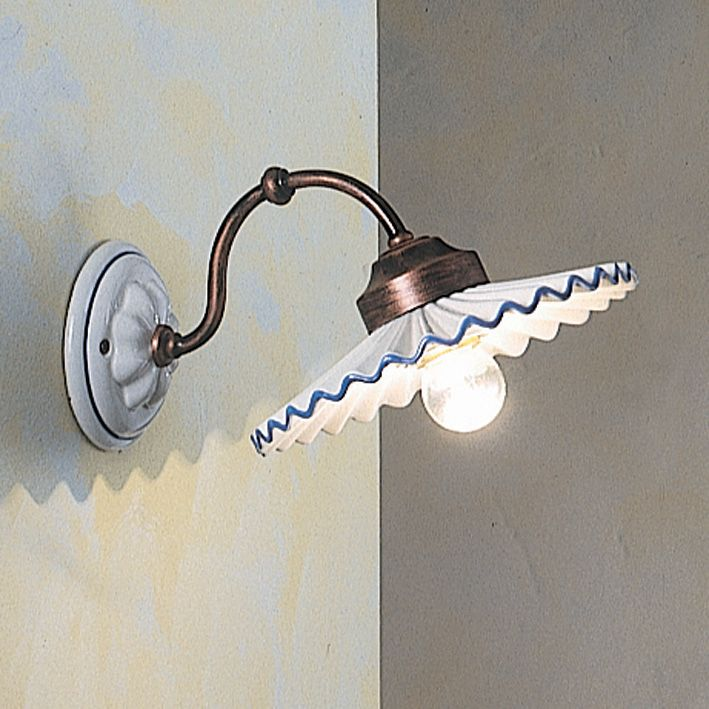 Rustic wall lamp with brass support and hand decorated ceramic shade.