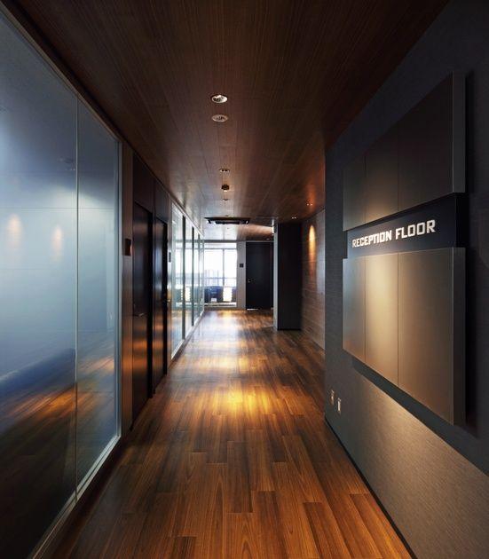 ツインバード工業株式会社様の納入事例/【アプローチ空間】お客様を奥へ奥へと導く、ダークウッドの床・壁・天井で構成したチューブ形状の空間。