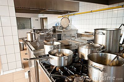 Interior of an industrial kitchen with big stoves and pans, cauldrons.