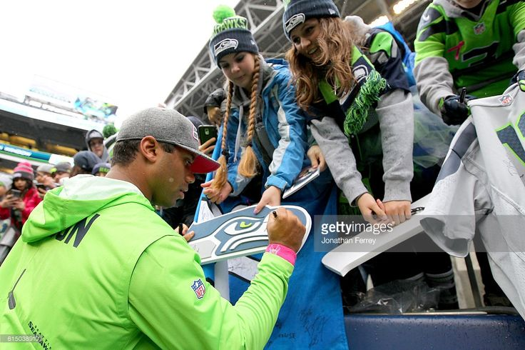 Quarterback Russell Wilson #3 of the Seattle Seahawks signs autographs before a game against the Atlanta Falcons at CenturyLink Field on October 16, 2016 in Seattle, Washington.