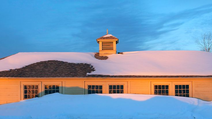 A setting sun colors a building nearly obscured by snow at Laudholm Farm in Wells. The farm's headquarters building is on the National Register of Historic Places, and the Wells Reserve maintains more than a dozen historic structures. Gregory Rec/Staff Photographer