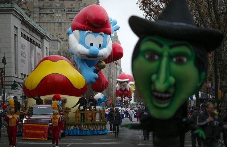 """Balloons float down Central Park West during the 88th Macy's Thanksgiving Day Parade in New York Nov York November 27,2014; the Papa Smurf and the Elf on a Shelf are the two balloons in this picture. The witch from """"The Wizard of Oz"""" is in the foreground."""