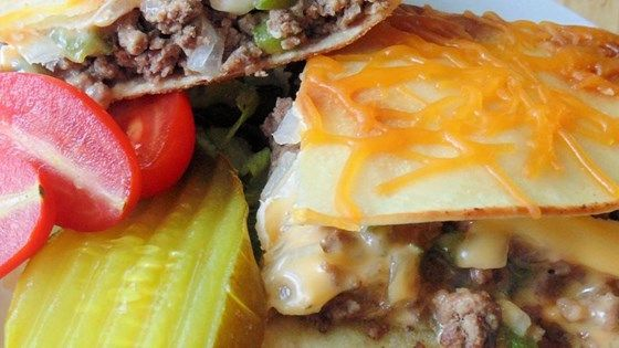 Replace burger buns with tortillas in this fun recipe mashup for cheeseburger quesadillas topped with cheese, tomato, lettuce, and onion.