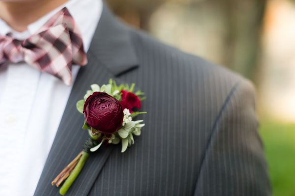 For jewel-toned wedding schemes, or those with dark neutrals, this maroon ranunculus boutonniere is very fitting.