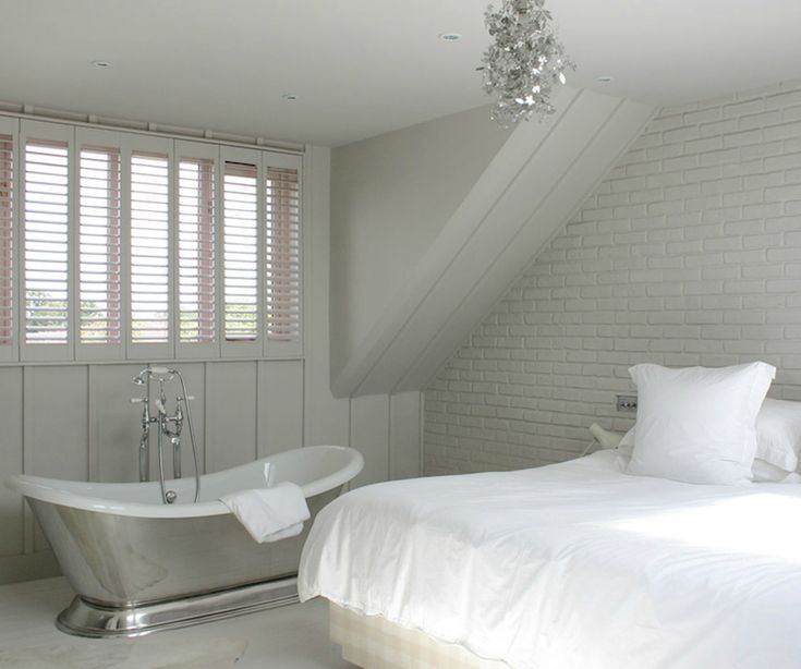 monochromatic bedroom design with exposed brick wall painted light gray gray paneled walls waterworks candide freestanding oval bathtub and sparkly