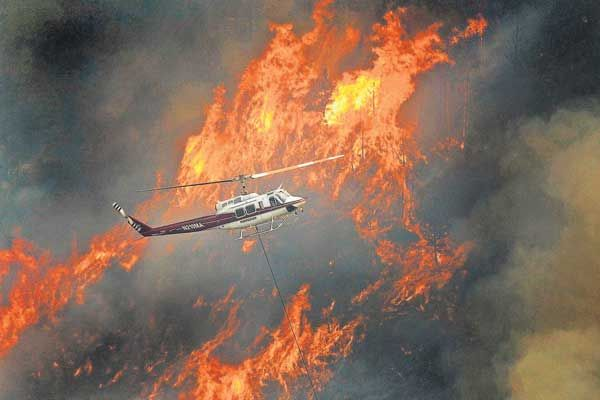 A helicopter flies through Poudre Canyon on Thursday as flames scorch the forest south of the river. (Photo by Karl Gehring, The Denver Post)