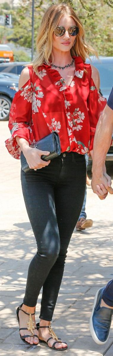 Who made  Rosie Huntington-Whiteley's jewelry, black clutch handbag, black skinny jeans, flat sandals, and red floral cut out shirt?
