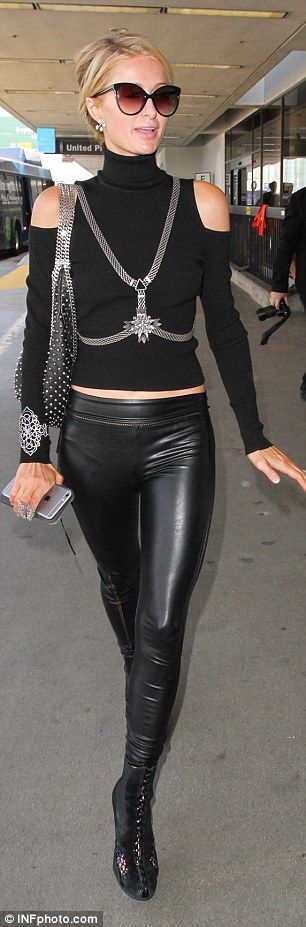 Flight fashion: The 35-year-old hotel heiress flaunted her lithe figure in a turtle neck which flashed her toned tummy along with a low slung pair of skintight leather pants with mesh cut-outs