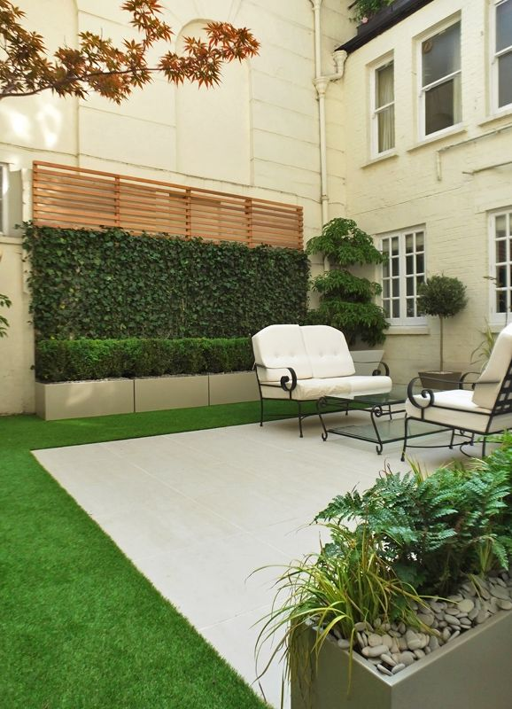 Topiary #courtyard in London with #tiles, white beige and sable planters, #artificial #grass, Ivy screen, cedar and Box hedging. Other planting include Phormium and Wheel tree.