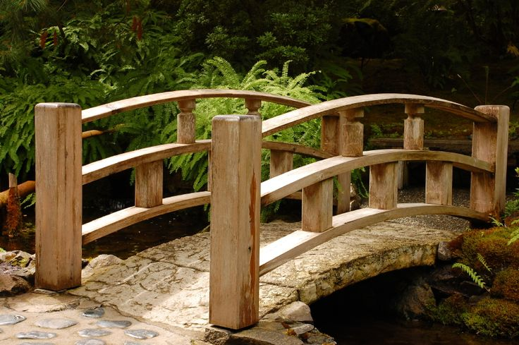 There is something so elegant about the smooth arches of a wooden bridge. This one has an aged stone path over mossy rocks and a shallow stream.