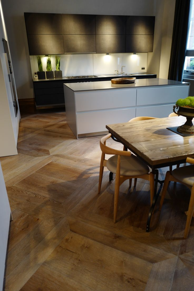Antique grey distressed engineered flooring enhances this kitchen diner