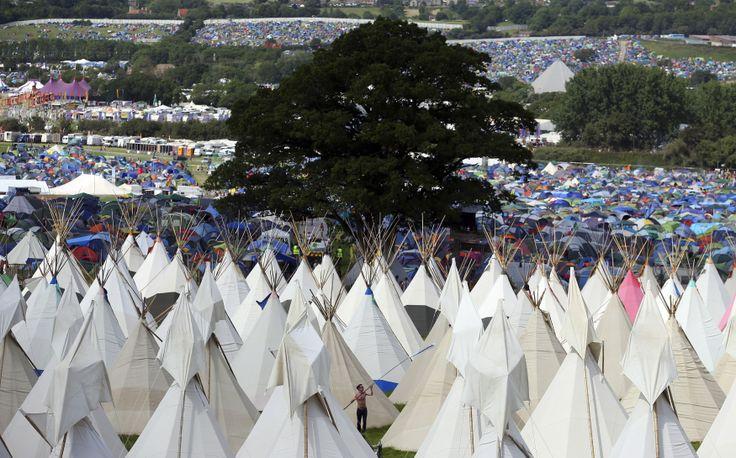 Warga Inggris yang menghadiri festival tadisional Glastonbury mendirikan tenda didi kota Somerset.