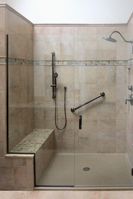 Spacious shower with built-in bench, grab bar, and additional shower head.