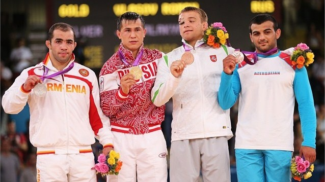 Roman Vlasov of Russia stands on the podium with his Gold Medal, Arsen Julfalakyan of Armenia (L) the Silver and Emin Ahmadov (R) of Azerbaijan and Aleksandr Kazakevic of Lithuania the Bronzes after their Men's Greco-Roman 74 kg Wrestling Gold Medal bout against Arsen Julfalakyan of Armenia on Day 9 at ExCeL