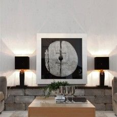 Symmetric living room with two black table lamps that create beautiful reflections.