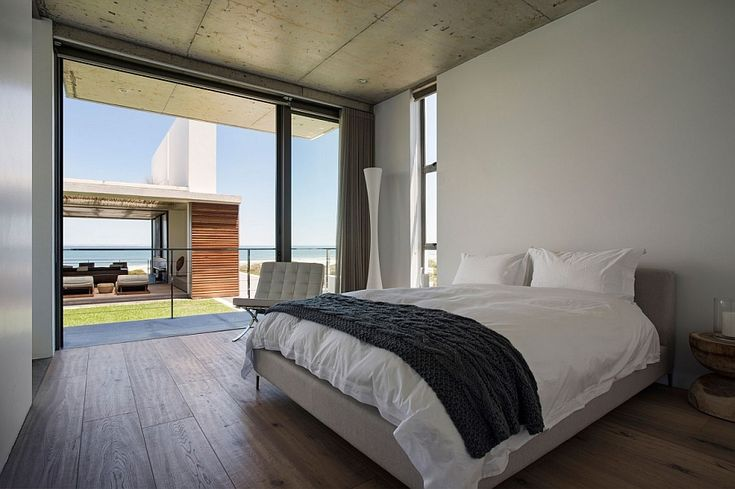 Serene bedroom overlooks the living area and the distant ocean - Decoist