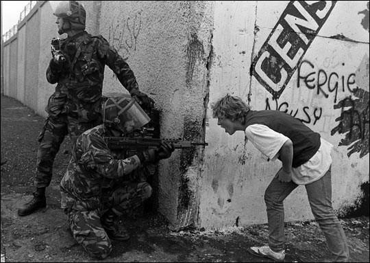 Un adolescente Irlandese urla contro i soldati Britannici durante disordini sociali in Irlanda del Nord