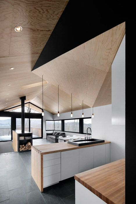 Bolton Residence by Nature Humaine, Quebec A chunk cut from one corner this black-painted block creates a recess to accommodate the kitchen, which has pale maple counter-tops and white units.