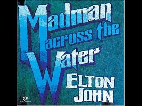 "Elton John - Madman Across the Water (1971) With Lyrics!  The title track from Elton John's 1971 album ""Madman Across the Water."" ""Madman"" was Davey Johnstone's first appearance on an Elton John album and he is featured on acoustic guitar on this track. Ray Cooper played percussion and Rick Wakeman played organ. This was before he joined the group Yes and found fame in his own right."