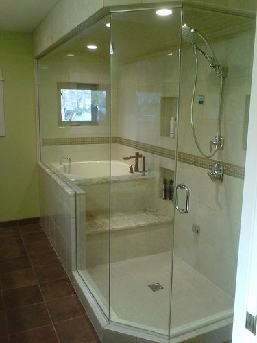 This tile steam shower features a large 9 foot long glass wall and a barrel ceiling that curves to help shed water droplets  The owners chose an eclectic mix of ceramic, glass, granite with chrome and bronze fixtures to complete this spa.