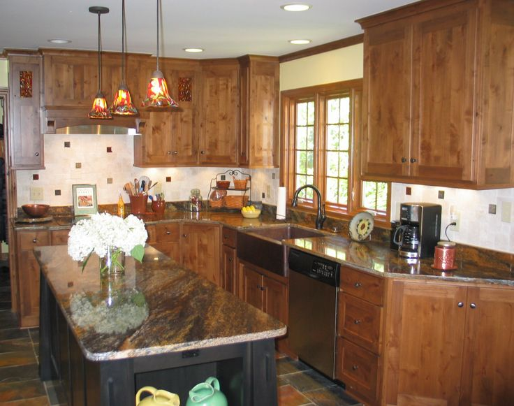 Knotty Alder Kitchen with Custom Glass Cabinet Inserts and Pendant Lights - designed by Kilpatrick Traditons Custom Cabinetry in Carmel, Indiana