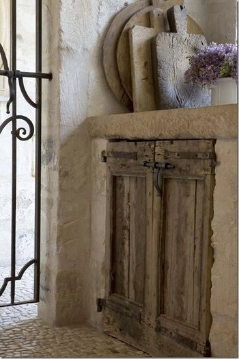 add antique doors to an outdoor kitchen with a limestone counter, rock walls, old bread boards for accent....pebble floor, iron