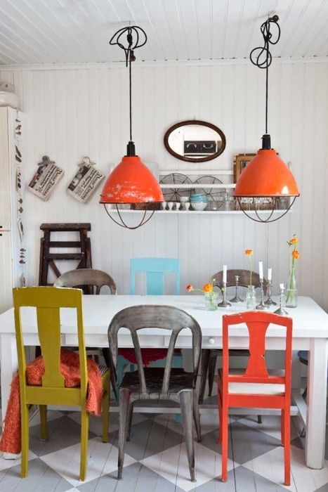 The colors in this casual modern dining room are playful and warm despite the otherwise white room. There is a charming modern farm style about this dining room with all it's little rustic touches. It's a great example of pulling off the look of different style dining room chairs.