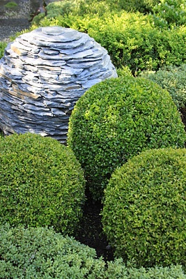 boxwood shrubs cut in orb shapes. Planting the right shrubs. Stone stacked garden sphere.