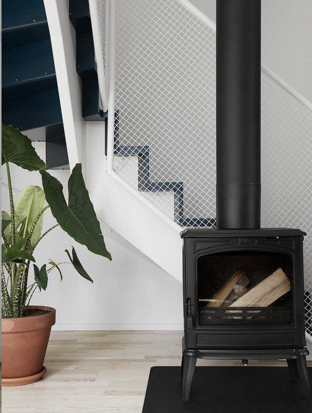 Poêle à bois design en bas de l'escalier graphique dans une grande maison scandinave simple mais cozy sur @decocrush - www.decocrush.fr