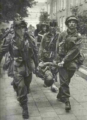British paratroopers carry a wounded comrade through the streets of Arnhem during Operation Market Garden. Possibly a German photo, taken following the surrender of the British contingent at Arnhem bridge.