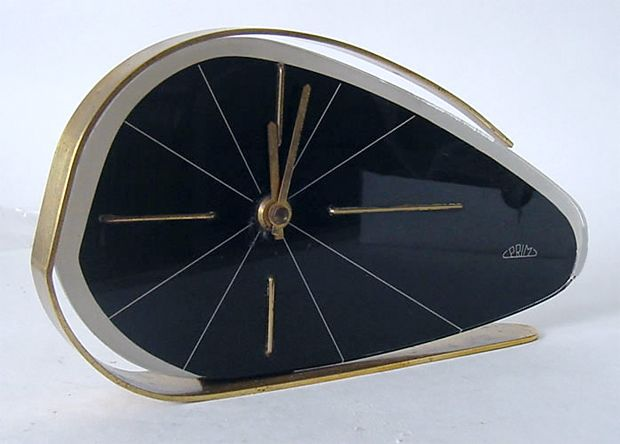 Table clock with black plastic face and brass hands and frame manufactured by Prim.  Year: c. 1960s