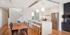 Designer kitchen, Smeg gas range, timber dining room table, pendant lighting, bar stools, stainless steel fridge, Pilcher Residential