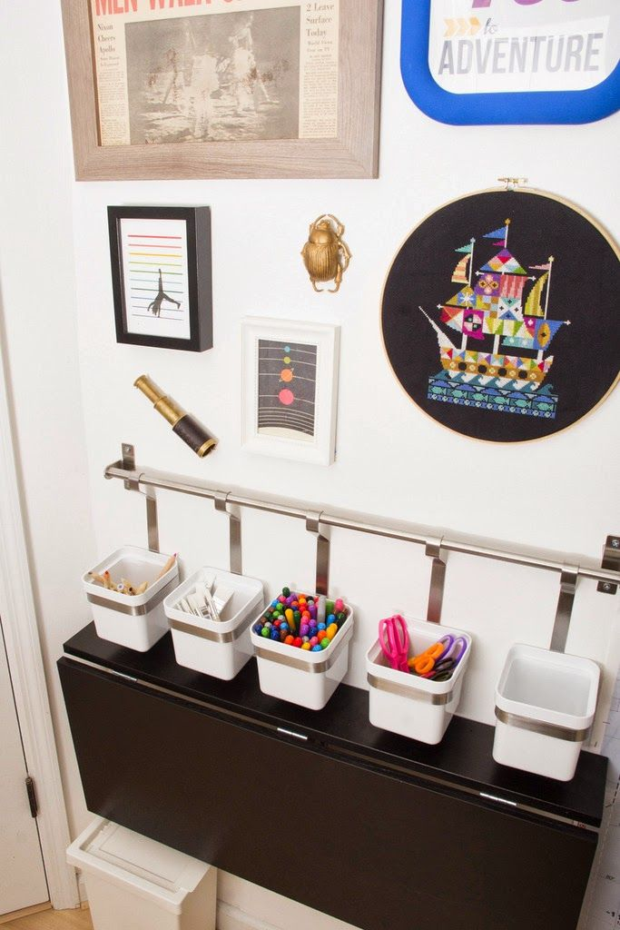 the fold-away desk behind the door is a dining table meant for small kitchens. it stows and sets up so easily that both kids can do it by themselves. art supplies are within reach hanging from the kitchen utensil rack.