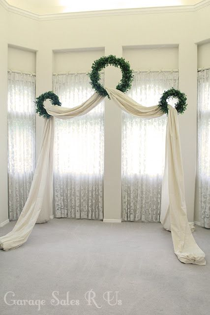 Backdrop of curtains  1.  curtains at windows  2.  add 3 wreaths 3.  add long fabric so drapes on floor and frames space