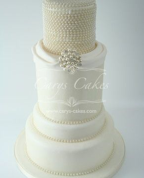 Simple stylish wedding cake, decorated with pearly lustre and pearls, finished off with a beautiful brooch