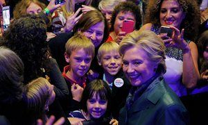 Clinton gaining ground as Obama's approval ratings go up – campaign live caption: Democratic presidential nominee Hillary Clinton poses with audience members at a Women for Hillary campaign finance event in Washington, DC, on Wednesday.