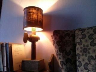 Lámpara de mesa. La base de madera tratada, el pie es una antigua llave de paso de grifo, con portalámparas antiguo y pantalla antigua teñida de negro. 50€