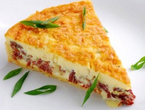 Torta de Liquidificador. Bata 1 ovo, 6 colheres de farinha de trigo, 5 colheres de queijo ralado, 1 pitada de orégano,1 colher (sobremesa) de fermento em pó, 1/2 cebola, 1 xícara de chá de leite, 1/2 xícara de chá de óleo e 1 pitada de sal. A massa deve ficar um pouco mais mole. Acenda o forno para pré-aquecer em temperatura média. Unte, derrame um pouco da massa para cobrir o fundo, depois acrescente o recheio e cubra com o restante da massa e leve ao forno até dourar por cerca de 30 min.