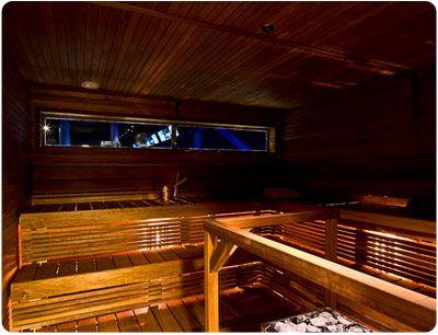 Falcon Business Park. Lämpöleppä puusta sauna. Epäsuora valaistus lauteiden alta puuritlilöiden välistä. Saunasta näkymä keilaradalle