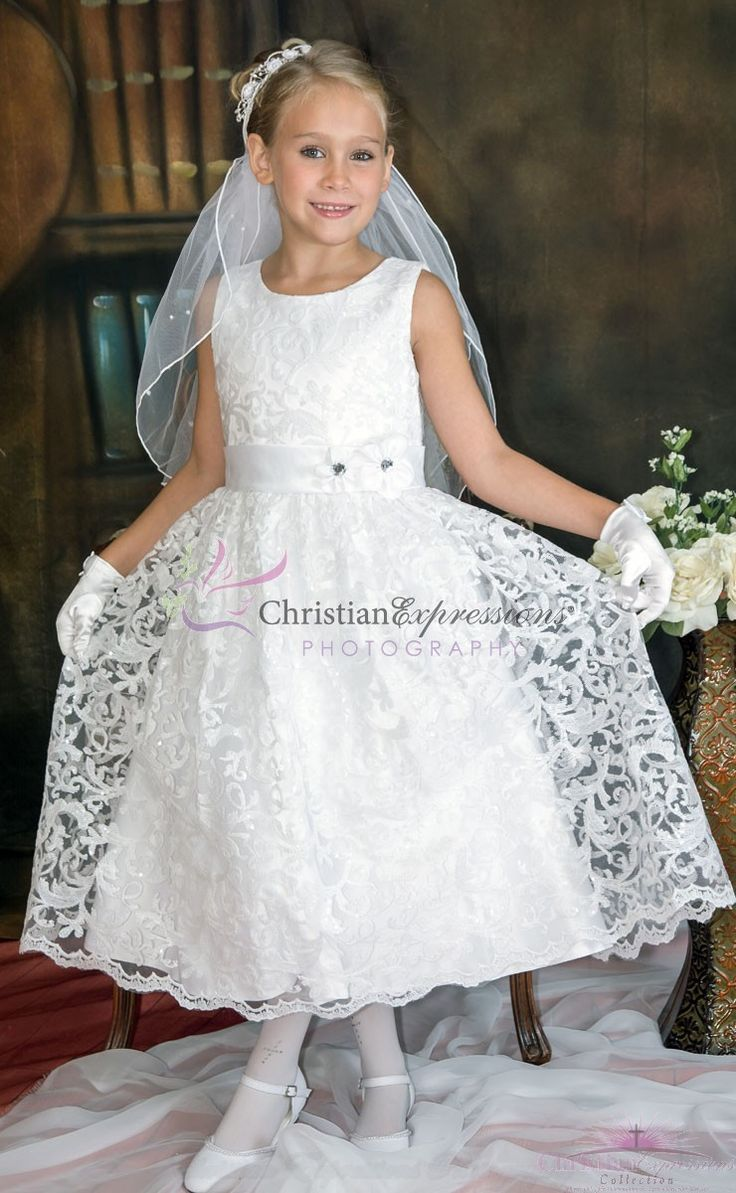 Sleeveless tea length first communion dress features a full sequined lace overlay skirt with scalloped hemline, pretty lace sequined bodice accented with a satin sash with rhinestone flower on waist . Zipper back with organza tie bow.