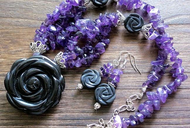 Masívny prívesok v tvare ruže z polodrahokamu onyx, je doplnený masívnymi kovovými kaplíkmi, ktoré plynule prechádzajú do troch radov ametystových zlomkov v krásnej fialovej farbe. Ďalej zlomky prechádzajú do menších onyxových ruží a jedného radu ametystových zlomkov  K náhrdelníku patria aj náušničky z rovnakého materiálu  Výrazný, elegantný a luxusný kúsok